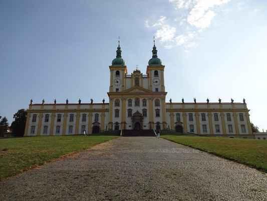 bazilika Navštívení Panny Marie na Svatém Kopečku Historie tohoto místa se začala psát na počátku 17. století, v době, kdy Evropou zmítala třicetiletá válka. Jméno, které bude navždycky spojováno se Svatým Kopečkem, je Jan Andrýsek, který na základě svého slibu zbudoval v letech 1629-1633 malou kapli zasvěcenou Panně Marii v lesích na východ od Olomouce. Již záhy bylo toto místo svědkem vyslyšení modliteb a trápení lidí, kteří je sem přicházeli ve víře odevzdat. Mnohá jsou dokumentována, ale naprostá většina zřejmě zůstává skryta. V průběhu dějin věhlas zdejšího místa stoupal a časem byla Panna Maria na Svatém Kopečku vzývána a uctívána jako Královna Moravy.
